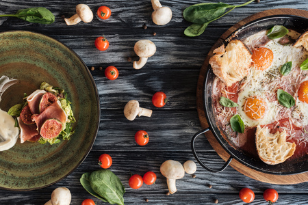 top view of delicious prosciutto, fried eggs and fresh vegetables on wooden table Фото со стока