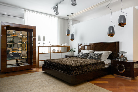 interior of modern light bedroom with lamps, shelves and brown bedsheets Banco de Imagens