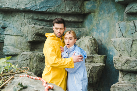 emotional young couple in raincoats terrified of snake Stock Photo