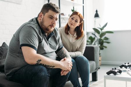 Novia con sobrepeso mirando triste novio en casa