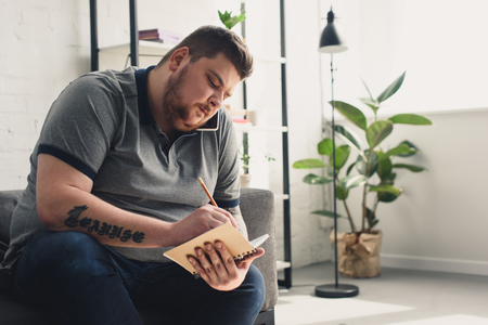 Handsome overweight man writing something to notebook on sofa at home
