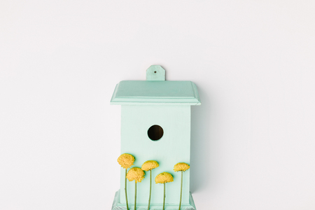 top view of blue birdhouse with yellow chrysanthemum flowers isolated on white Stockfoto