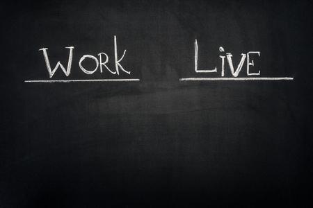 Work and Live underlined inscription on dark chalkboard