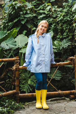 beautiful young woman in blue raincoat and yellow rubber boots in rainforest