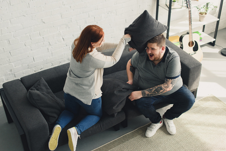 boyfriend and girlfriend fighting with pillows on sofa at home
