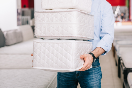 partial view of man holding pile of folding mattresses in hands in furniture store