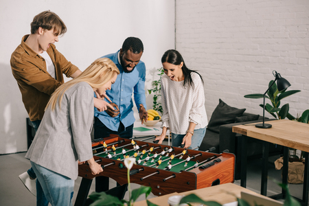 businesswomen playing table football and two male colleagues pointing on board game Stock Photo