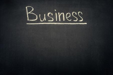 Business underlined inscription on dark chalkboard