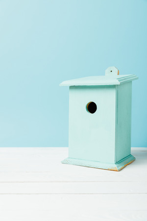 close up view of blue birdhouse on wooden surface isolated on blue Stockfoto
