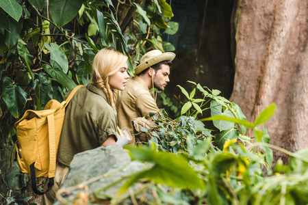 active young couple in safari suits hiking in jungle and looking somewhere impressed 版權商用圖片