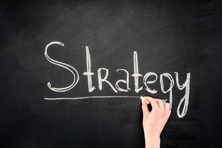 Hand writing Strategy underlined inscription on chalkboard Фото со стока