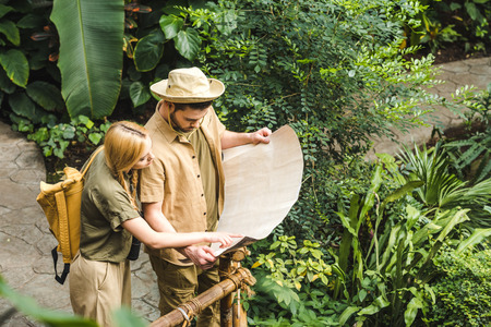 beautiful young couple in safari suits with map in jungle