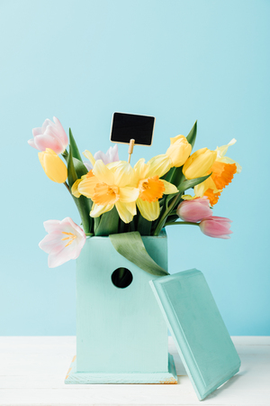 close up view of beautiful bouquet of flowers with blank chalkboard in birdhouse on wooden tabletop isolated on blue Stock Photo