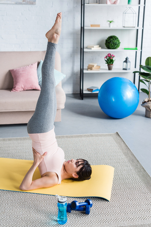 beautiful young woman practicing yoga in Supported Shoulder Stand (Salamba Sarvangasana) at home Stock Photo - 106898306