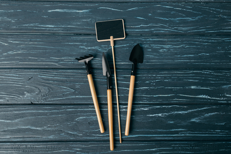 flat lay with arranged gardening tools and empty chalkboard on wooden tabletop