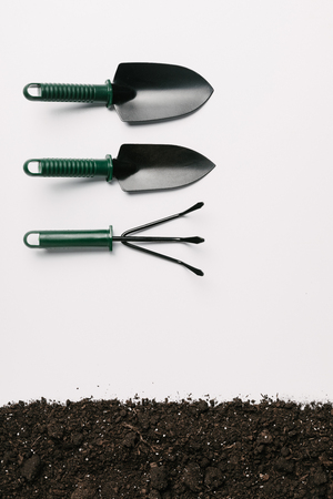 top view of arranged gardening tools and ground isolated on white