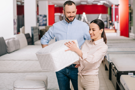 couple choosing folding mattress together in furniture store with arranged mattresses Stock Photo