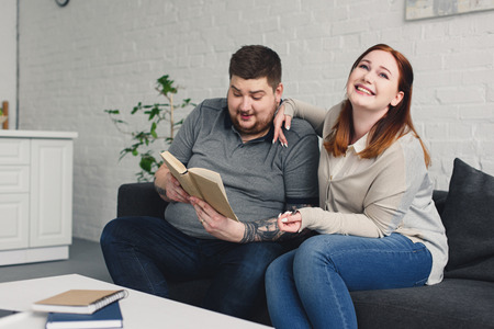boyfriend reading book to smiling girlfriend at home