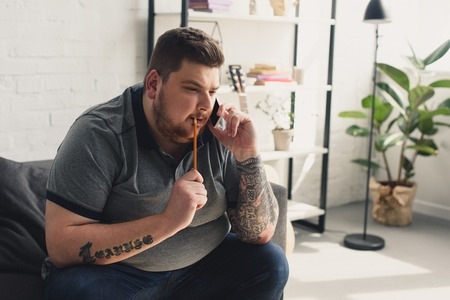handsome man talking by smartphone and biting pencil at home
