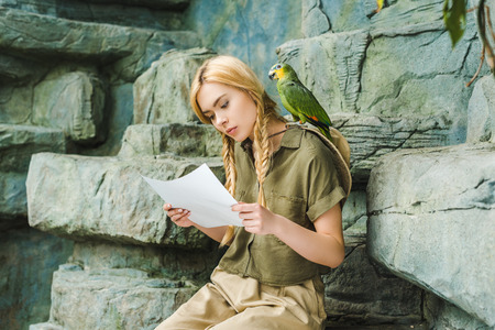 beautiful young woman in safari suit with parrot on shoulder and map sitting on rocks 写真素材