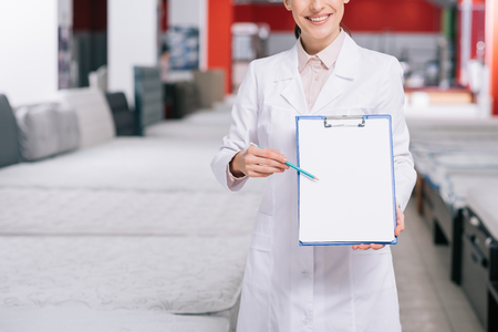 cropped shot of smiling shop assistant in white coat pointing at empty notepad in hand in furniture shop with arranged mattresses Фото со стока