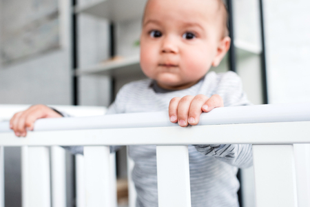 close-up portrait of adorable little child in baby cot looking at camera Stock fotó