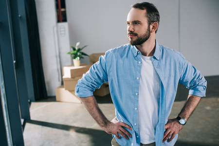 handsome bearded man standing with hands on waist and looking away during relocation Stockfoto