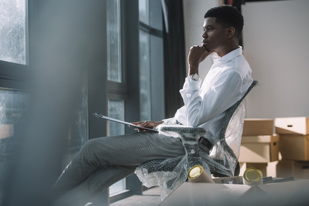 young african american businessman holding clipboard and looking at window while sitting in new office during relocation