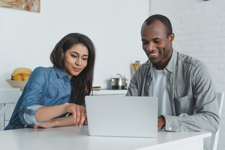 happy african american girlfriend and boyfriend looking at laptop at home Stock Photo