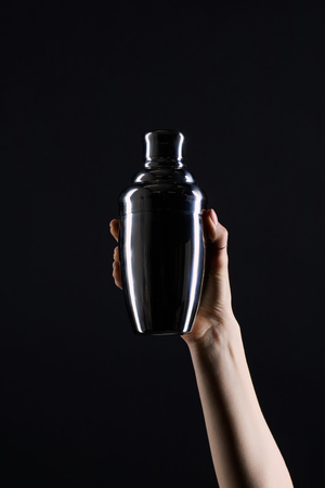 cropped shot of woman holding cocktail shaker isolated on black 免版税图像