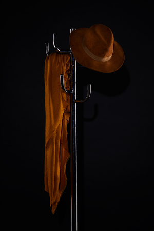 scarf and hat hanging on coat rack isolated on black