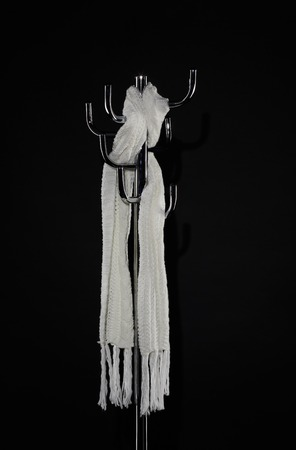 white scarf hanging on coat rack isolated on black Foto de archivo - 107970152
