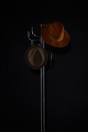 hats hanging on coat rack isolated on black