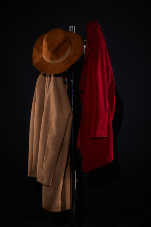 coats and hat hanging on coat rack isolated on black