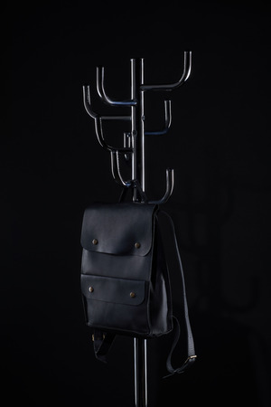 black leather backpack hanging on coat rack isolated on black Zdjęcie Seryjne