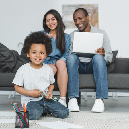 african american son looking at camera while drawing on floor at home Stock Photo