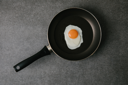 top view of frying pan with tasty fried egg on grey 版權商用圖片