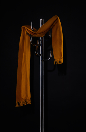 yellow scarf hanging on coat rack isolated on black Foto de archivo - 106755950