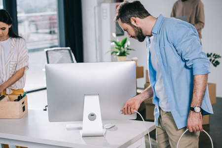 man holding plug from desktop computer while relocating with coworkers in new office