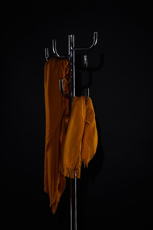 yellow scarves on coat rack isolated on black Stockfoto - 106756052