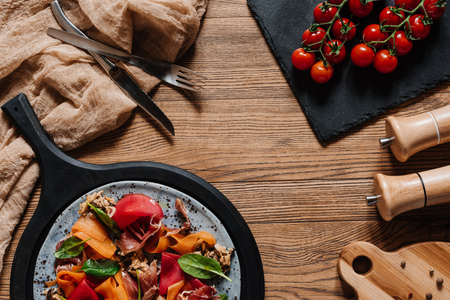 Salad with mussels, vegetables and jamon, fork with knife and fresh tomatoes on wooden table
