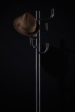 Sombrero clásico en el estante de rack aislado en negro Foto de archivo - 107113357