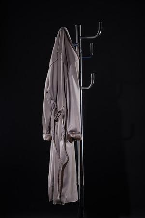 trench coat hanging on coat rack isolated on black