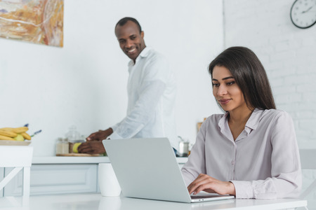 african american girlfriend using laptop and boyfriend cooking at kitchen Stock Photo