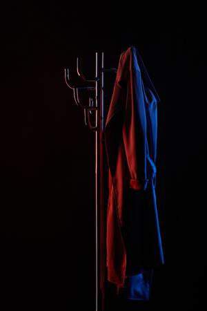 Escudo colgando en estante de rueda bajo luz de tonos aislados en negro Foto de archivo - 107115252