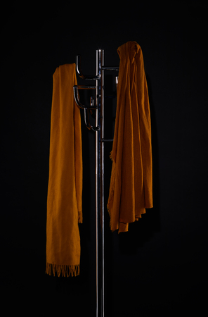 two scarves on coat rack isolated on black