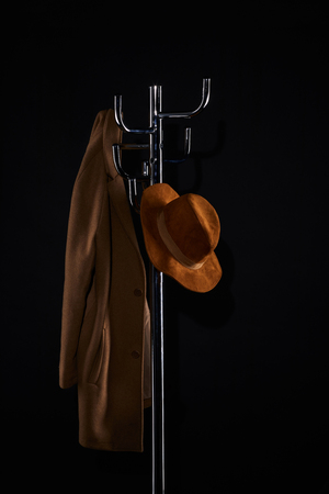 hat and coat hanging on coat rack isolated on black Banco de Imagens