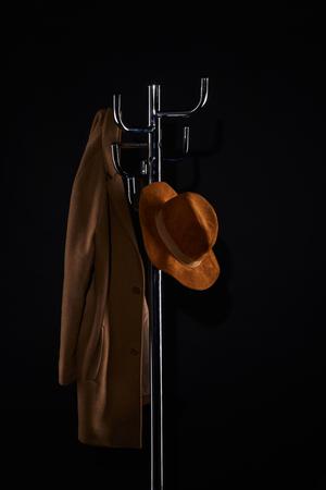 Sombrero y abrigo colgando de perchero aislado en negro