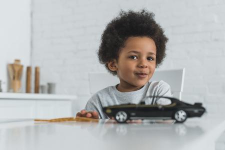 schattige Afro-Amerikaanse jongen aan tafel zitten met auto speelgoed en camera thuis kijken Stockfoto