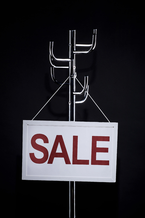 sale signboard hanging on coat rack isolated on black Foto de archivo - 106710681